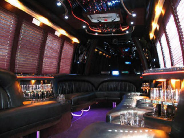 image is showing a party bus interior - black seats and wine glasses