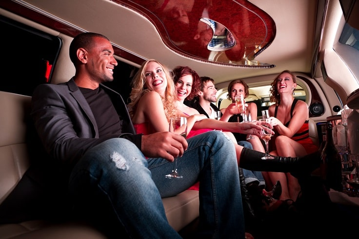 image is showing a group of happy people inside a limousine