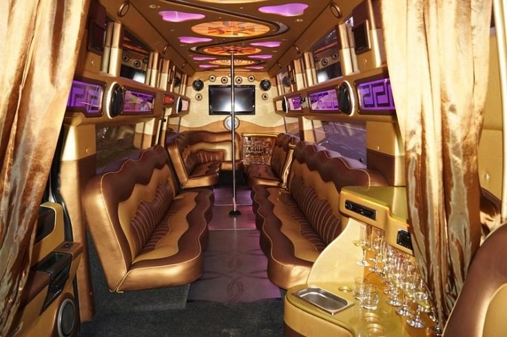 golden party bus interior with pole and tv