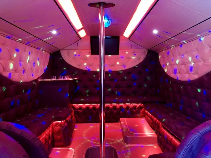 pink and purple party bus interior with a pole
