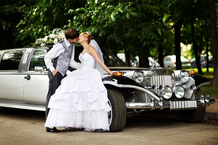 image is showing kissing newlyweds and old fashion limo